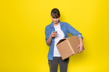 isolated woman on yellow with cardboard box