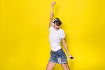 young woman listening music on yellow background
