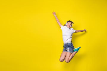 young woman listening music and jumping on yellow background