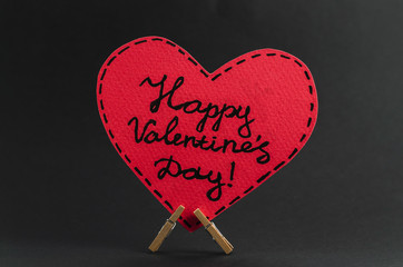Red heart on the clothespin with the greeting happy Valentines day on dark background.