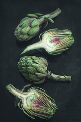 Opened fresh artichoke on the  dark background. Ingredients of southern Italian cuisine. Vertical format