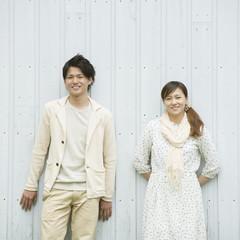 壁に寄りかかり微笑むカップル