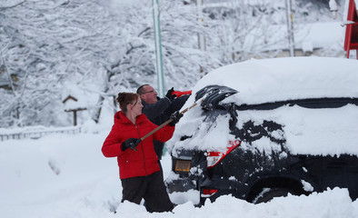 Villagers clear snow from a car in Leadhills, Scotland