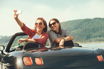 Two female freinds take a selfie photo in cabriolrt car during their summer voyage