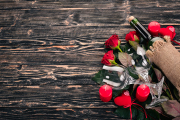 A bottle of red wine and a bouquet of red roses. Valentines day. On a wooden background. Top view. Free space for your text.