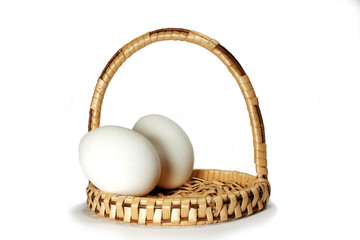 Wicker basket with two white Easter eggs isolated on a white background