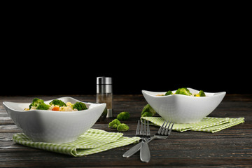 Delicious rice pilaf with broccoli in bowls on wooden table
