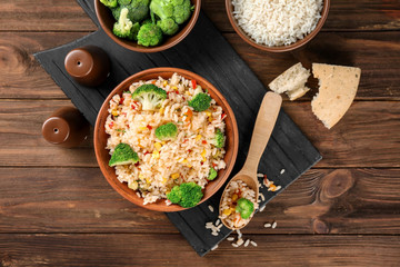 Delicious rice pilaf with broccoli in bowl on wooden table