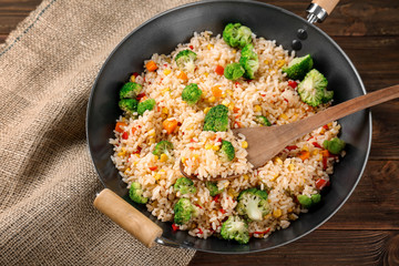 Delicious rice pilaf with broccoli in wok on wooden table