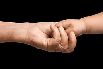 Hands of elderly man and baby on dark background