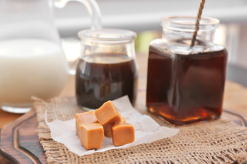 Tasty caramel candies on wooden board
