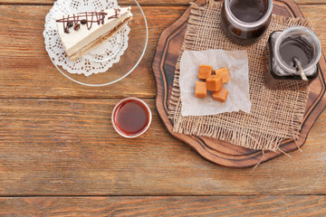 Composition with tasty candies and caramel sauce on table