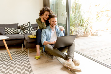 Young couple sitting on floor and using notebook.