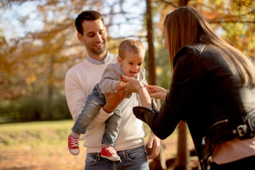 Happy young parents with baby boy in autumn park