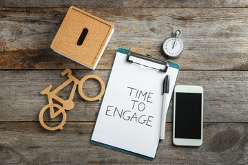 Composition with mobile phone, stopwatch, toy bicycle and phrase TIME TO ENGAGE on wooden background