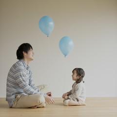 風船を持つ女の子と父親