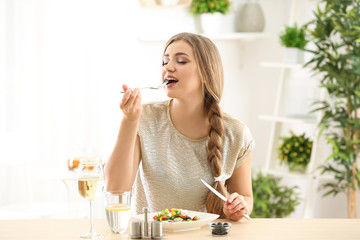 Young beautiful woman eating fresh salad at home