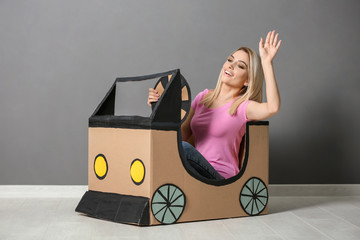 Young woman dreaming of buying own auto while playing with cardboard car indoors