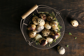 Quail eggs in metal basket on wooden table