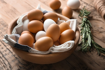 Chicken eggs in bowl on wooden table