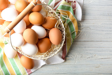 Chicken eggs in metal basket on wooden table