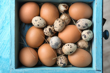 Quail and chicken eggs in wooden drawer