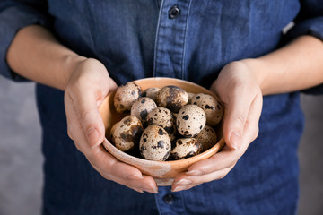 Woman holding bowl with quail eggs, closeup