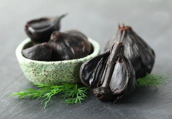 Bowl with black garlic (Allium sativum) on table