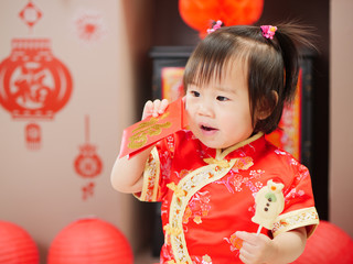 """Chinese baby girl  traditional dressing up with a """"FU"""" means """"lucky"""" red envelope,some """"FU"""" means """"lucky""""greeting card on the wall"""