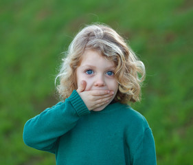 Surprised blond child covering his mouth