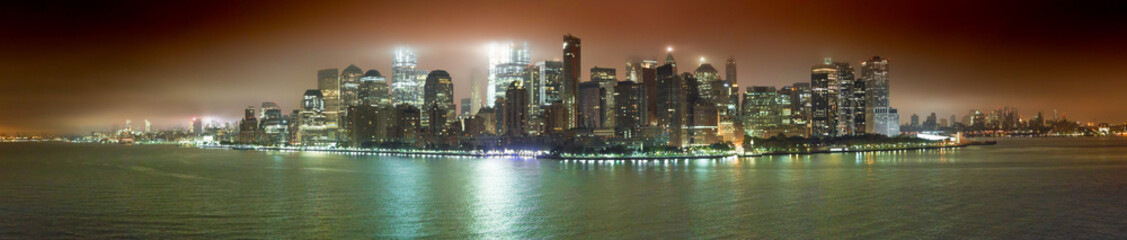 View of the Island of Manhattan during an early sailing, with the lights of the city and fog giving a spectacular result