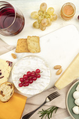 Various types of cheese with wine on a light background