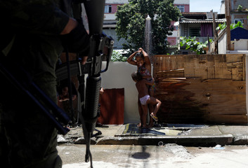 Children play under a shower at an alley of Manguinhos slum as Armed Forces members patrol during an operation against drug gangs in Rio de Janeiro