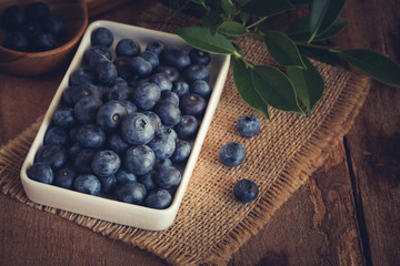 Blueberry in a white bowl on wood table