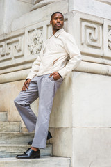 Portrait of Young Handsome African American Man in New York. Young black man wearing light color jacket, gray pants, black leather shoes, standing against vintage marble wall, looking around, relaxing