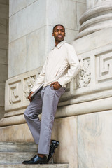 Young African American Man wearing light color jacket, gray pants, black leather shoes, holding laptop computer, standing on stairs against vintage wall on campus in New York, looking around, relaxing