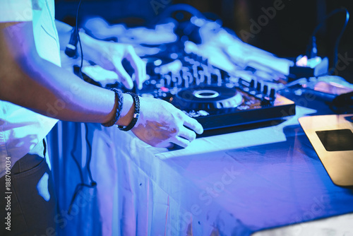 dj hands on stage mixing disc jockey and mix tracks on sound mixer