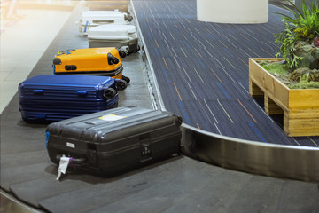 suit case on luggage conveyor belt at baggage claim in airport terminal.