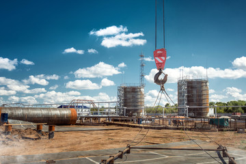 Constuction of an oil derrick, big oil tanks on the background.