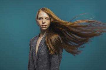 Attractive redhead woman shaking hair