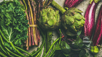 Flat-lay of green and purple vegetables over grey concrete background, top view. Local seasonal produce for healthy cooking. Eggplans, green beans, kale, asparagus, artichoke, basil. Clean eating