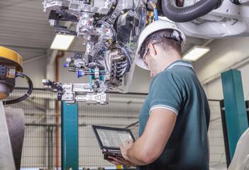 Ingenieur prüft Roboter bei Inbetriebnahme einer Produktionsanlage für Automobile