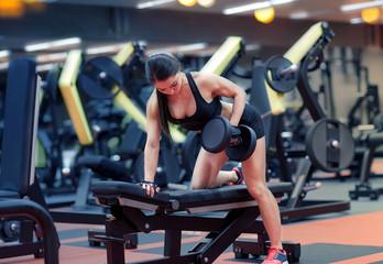 młoda kobieta wyginanie mięśni z hantle w siłowni