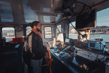 Young Capitan With Beard Stands At The Helm And Controls The Ship, View From Inside Captain's Cabin