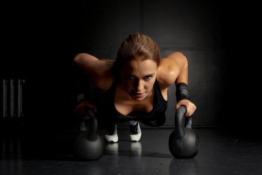 Woman doing push-ups exercises on kettlebells