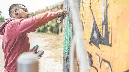 Young street artist painting with color spray on the wall - Contemporary graffiti artist at work - Urban lifestyle, modern street art and youth concept