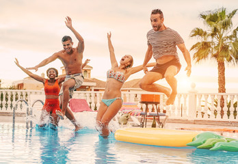 Group of happy friends drinking jumping in pool sunset party