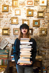 Young woman holding stack of books in library
