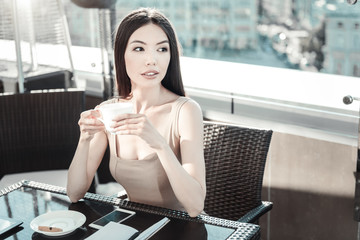 Wait for meeting. Pretty beautiful calm girl sitting in the restaurant holding cup of coffee and waiting.