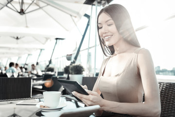 Useful gadgets. Pretty pleasant smiling girl sitting in the restaurant using her tablet and drinking coffee.